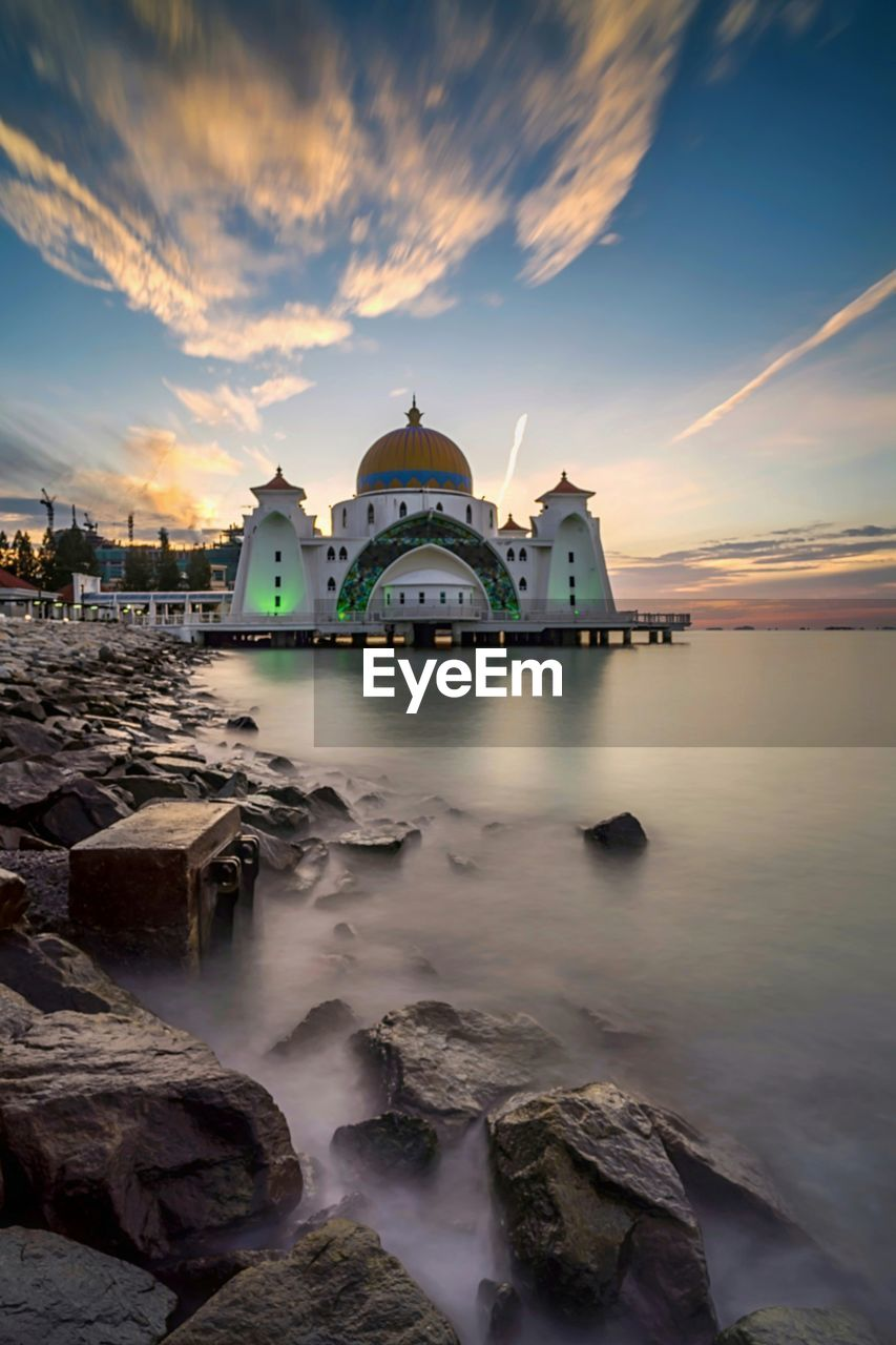 sky, water, sunset, cloud - sky, architecture, built structure, religion, nature, place of worship, belief, long exposure, building exterior, sea, spirituality, scenics - nature, rock, no people, solid, dome, outdoors