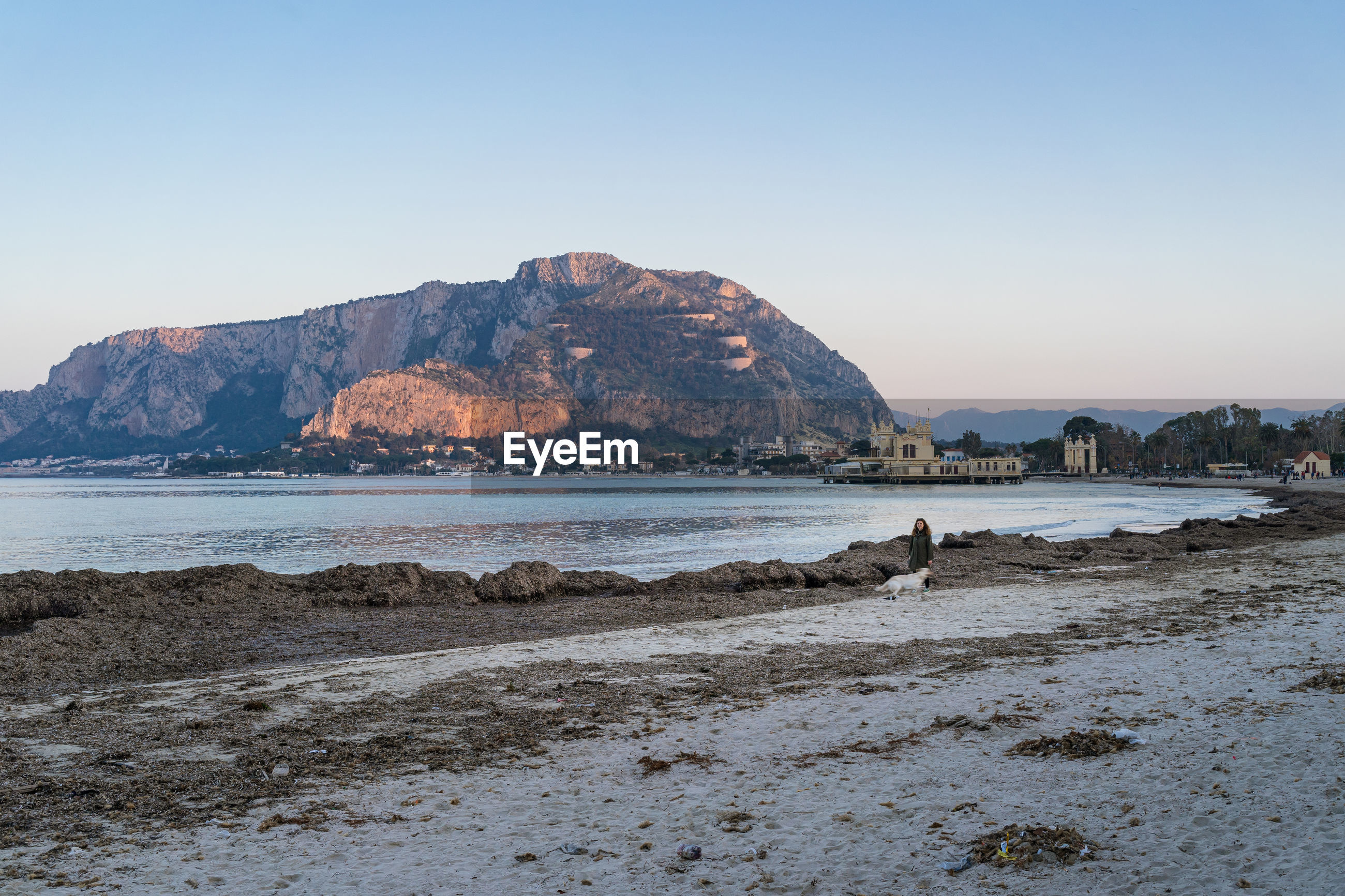 SCENIC VIEW OF BEACH AND MOUNTAINS AGAINST CLEAR SKY