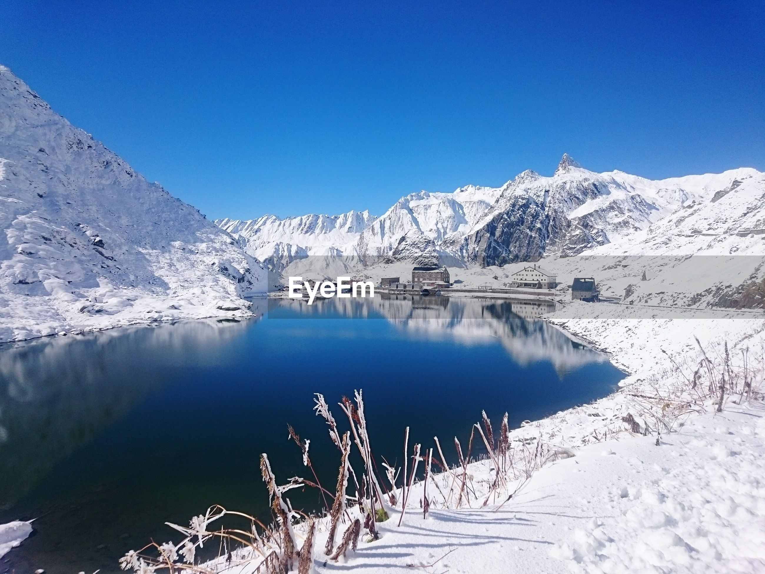 Scenic view of lake amidst snowcapped mountains against clear blue sky