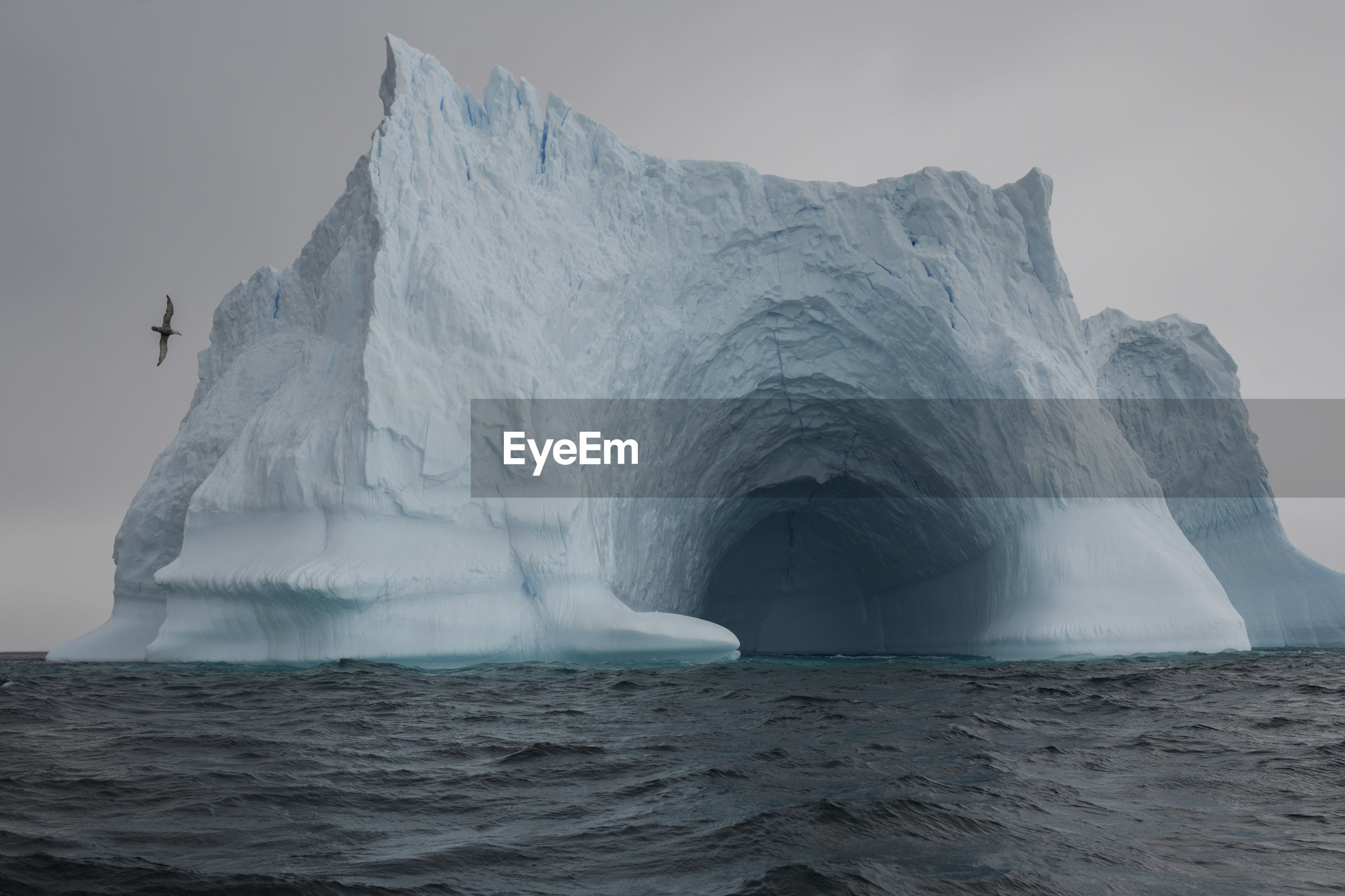 Scenic view of ice cave in sea against sky during winter