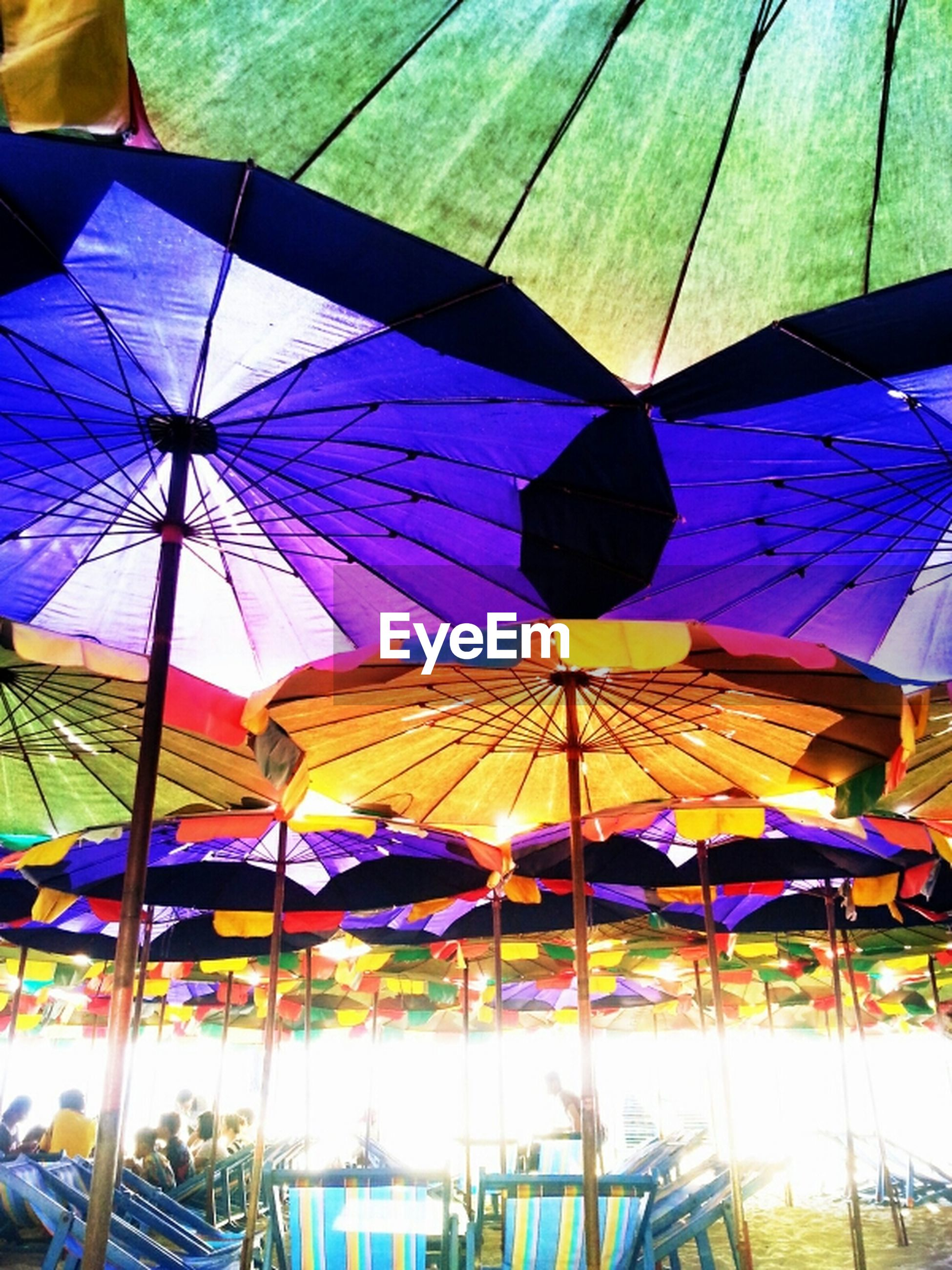 multi colored, umbrella, blue, colorful, low angle view, hanging, parasol, built structure, sunlight, flag, day, architecture, creativity, beach umbrella, pattern, decoration, fabric, art and craft, no people, outdoors