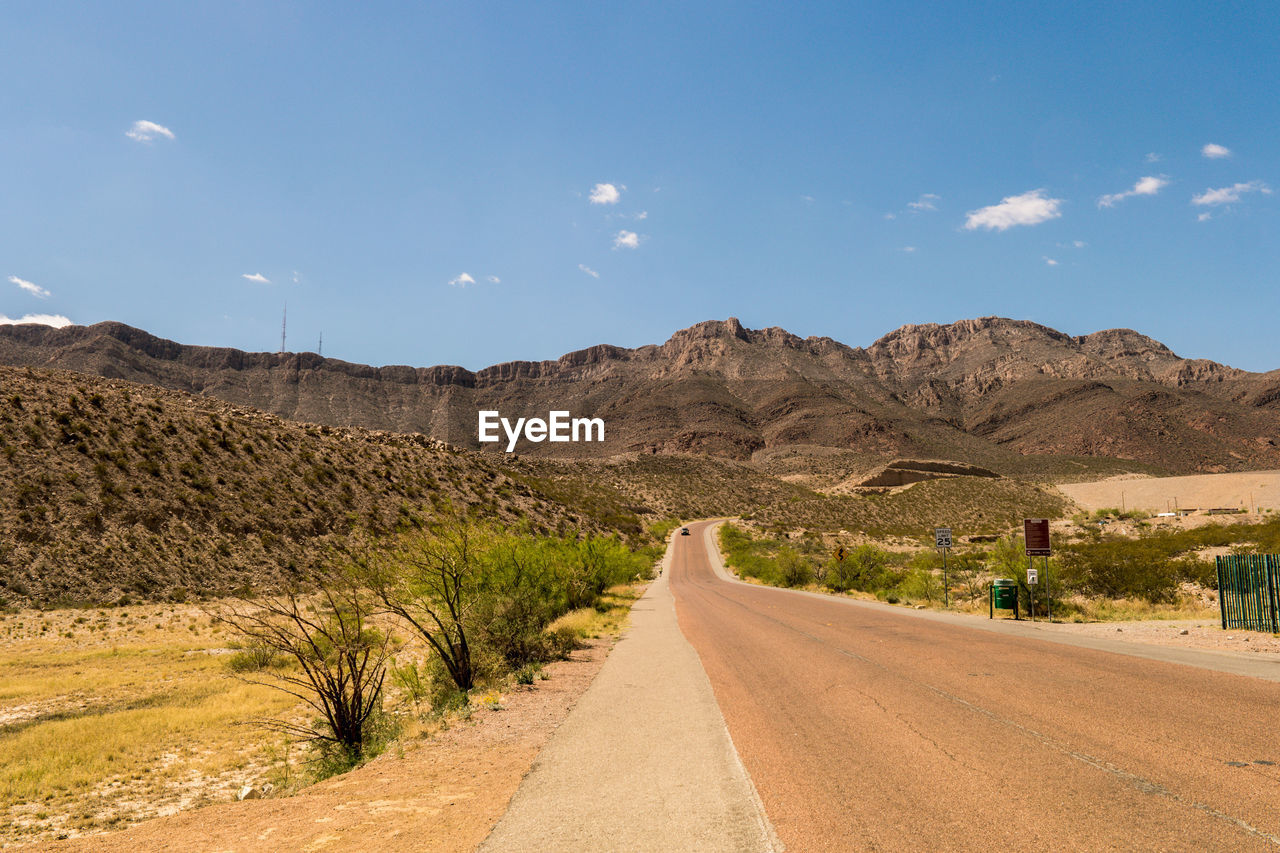 road, sky, mountain, the way forward, direction, transportation, scenics - nature, beauty in nature, landscape, environment, nature, tranquil scene, non-urban scene, tranquility, mountain range, diminishing perspective, day, cloud - sky, empty road, no people, outdoors, arid climate, climate, long