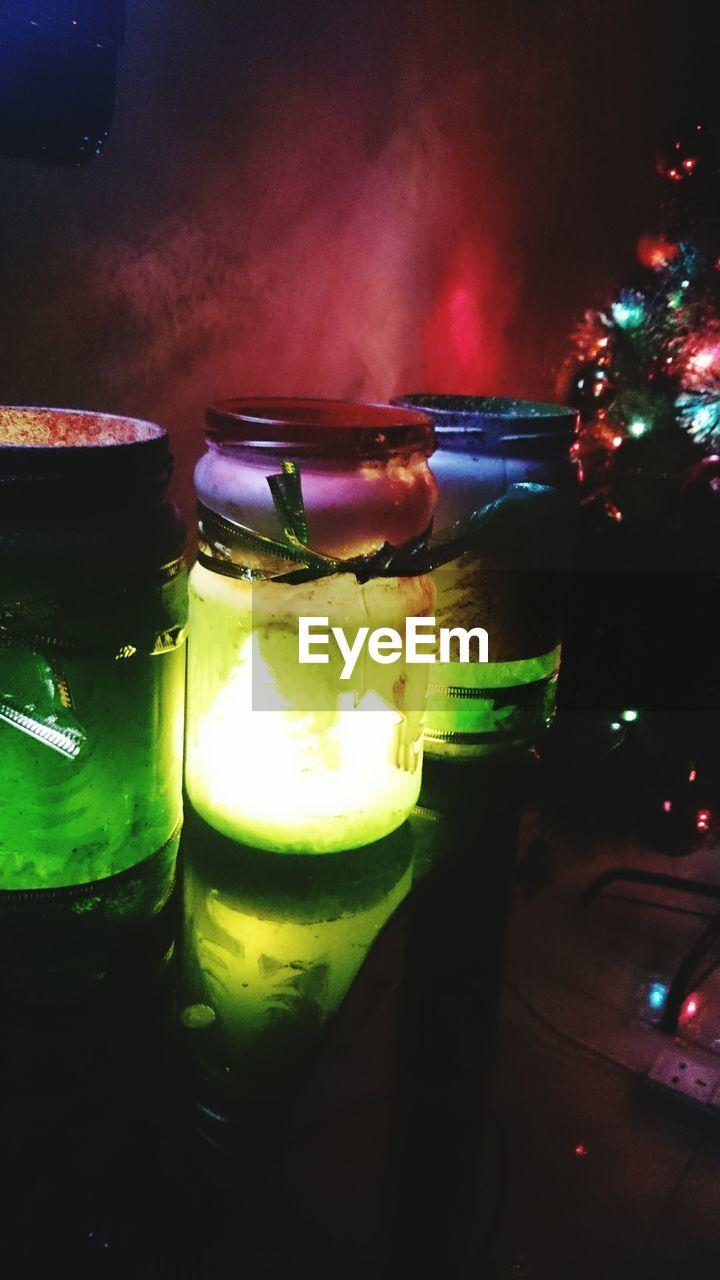 Close-Up Of Illuminated Jars On Table