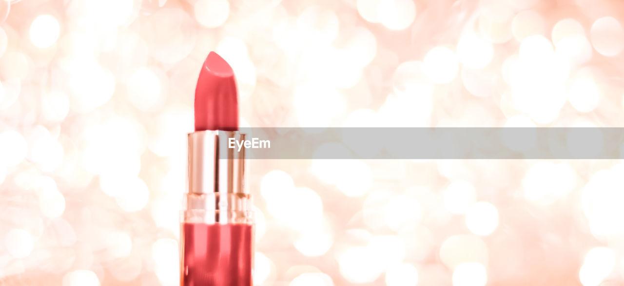 Close-up of red lipstick against illuminated light