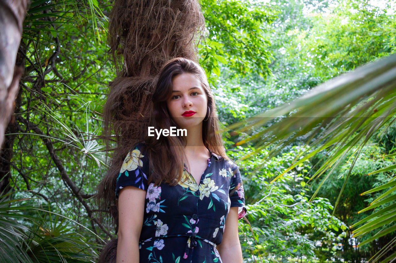 Portrait of beautiful young woman against tree trunk in forest