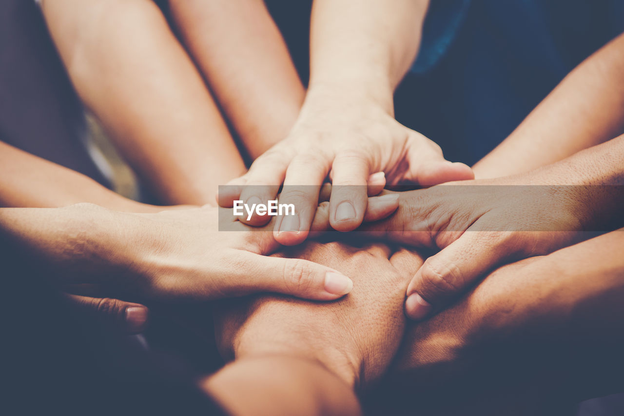 Close-Up Of Stacking Hands While Huddling Outdoors