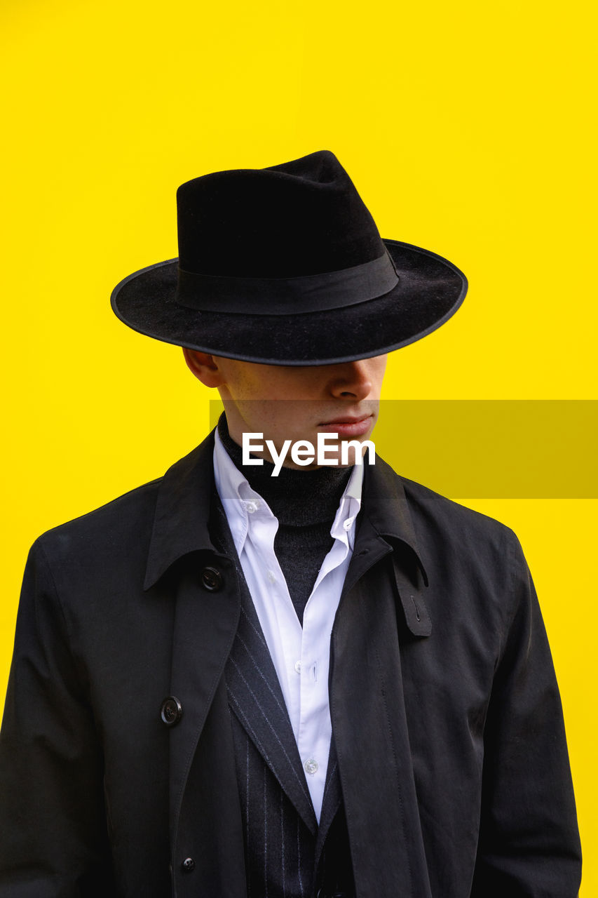clothing, hat, suit, front view, one person, well-dressed, formalwear, indoors, studio shot, yellow, young men, wall - building feature, waist up, men, real people, business, standing, black color, young adult, lifestyles, yellow background, menswear, teenager, teenage boys