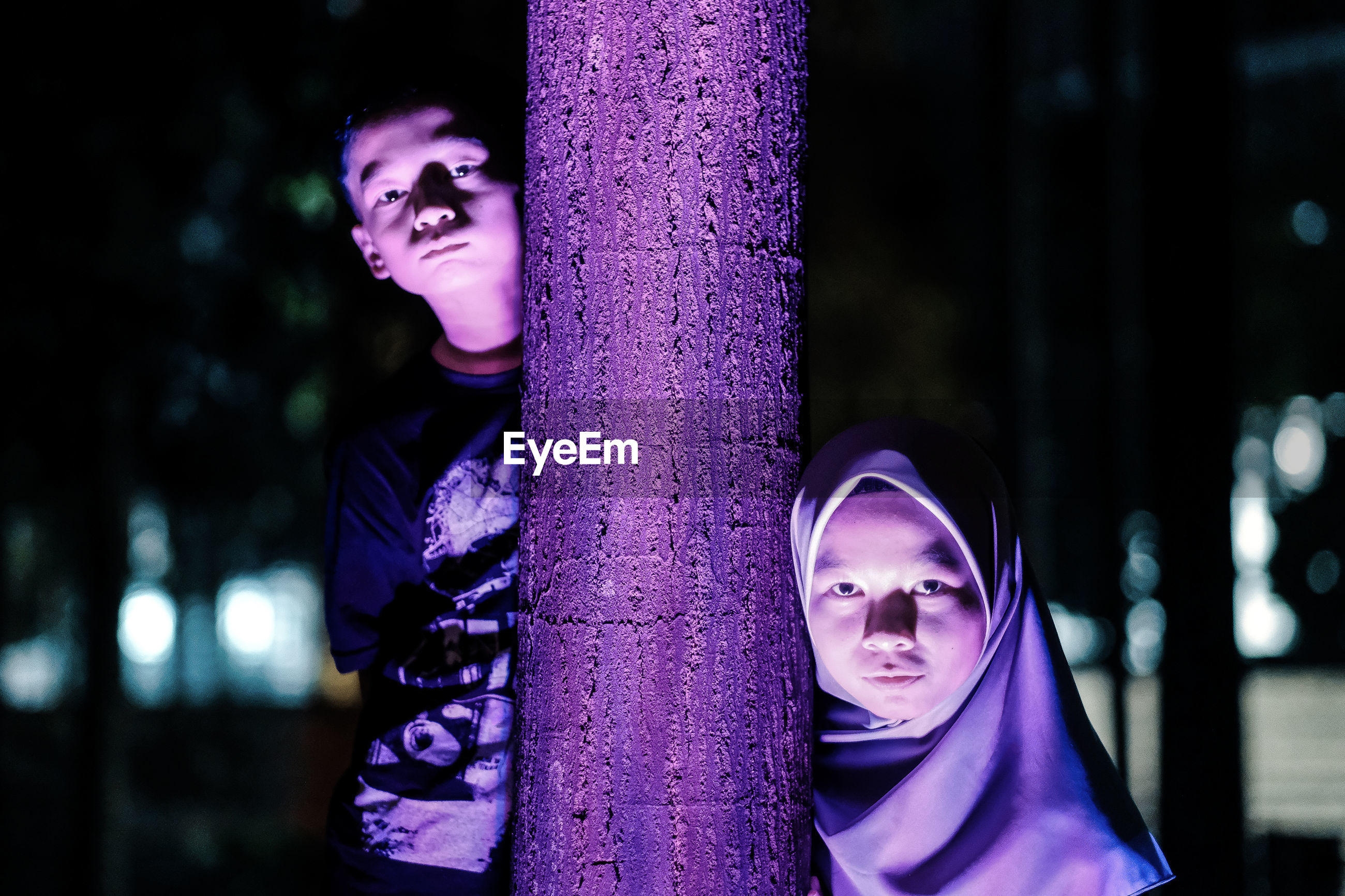 Portrait of siblings standing by tree trunk at night