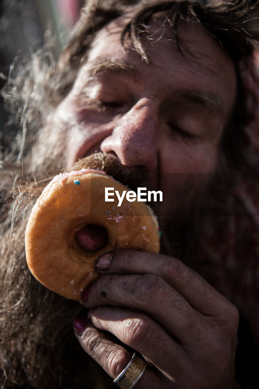 Close-up of man eating donut