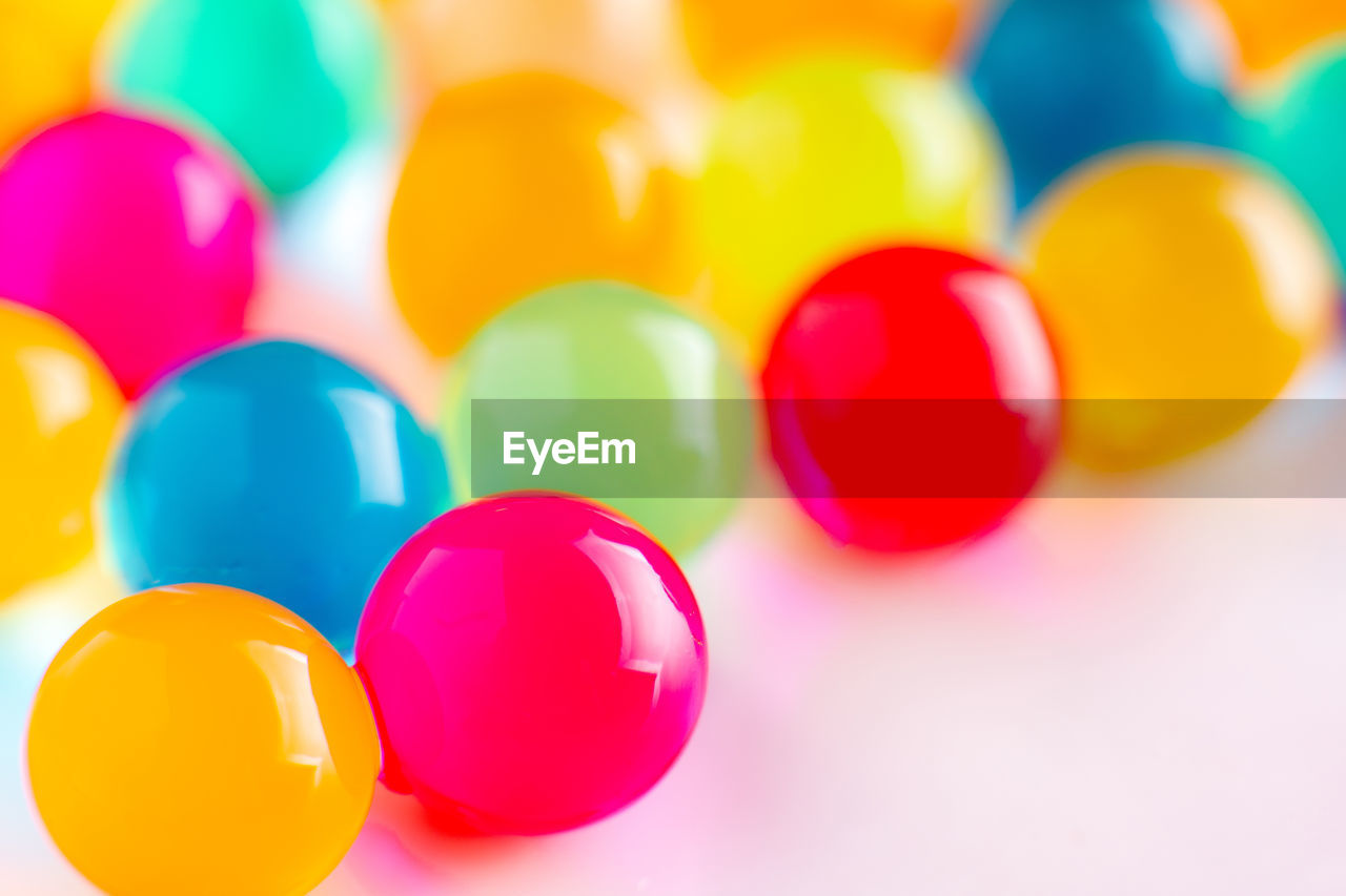 multi colored, indoors, no people, close-up, still life, large group of objects, selective focus, variation, balloon, choice, celebration, high angle view, shape, decoration, yellow, group of objects, design, focus on foreground, red