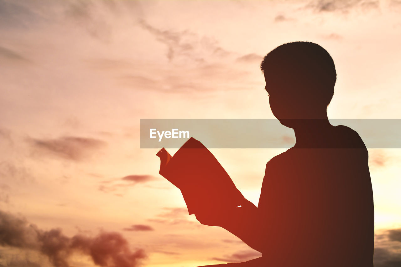 Silhouette Boy Reading Book Against Sky During Sunset