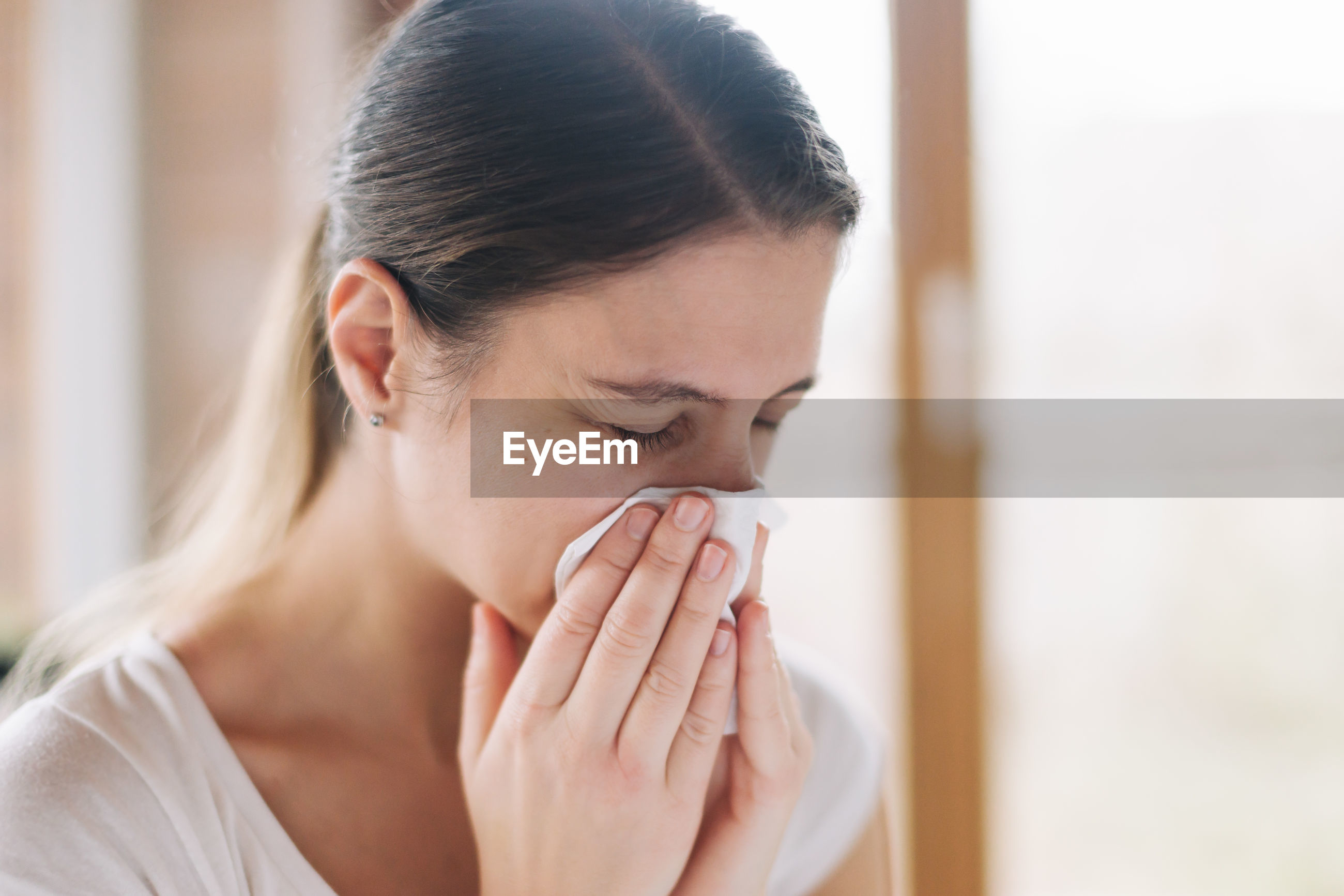 Close-up of ill woman blowing nose in tissue at home