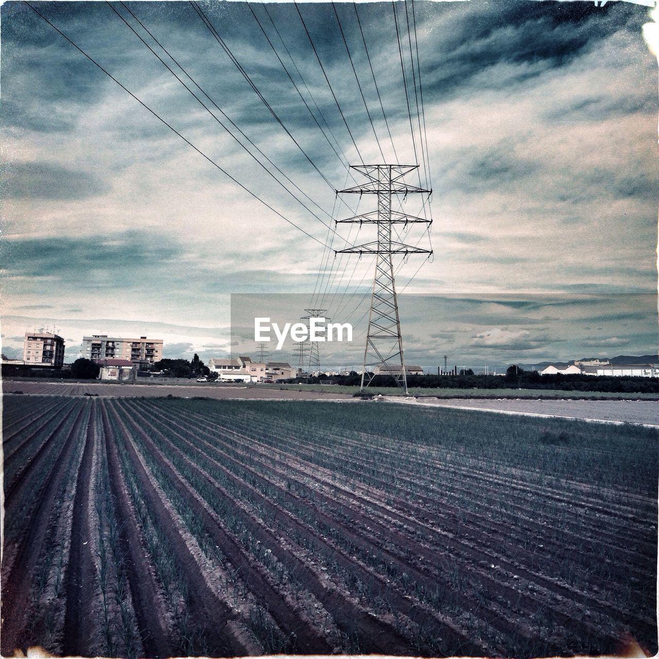 Electricity Pylon By Farm Field Against Sky