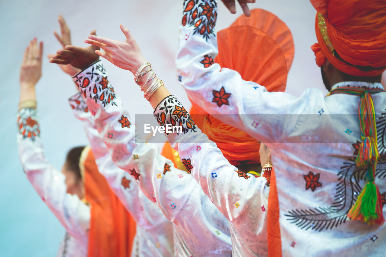 Rear View Of People In Traditional Clothing With Arms Raised