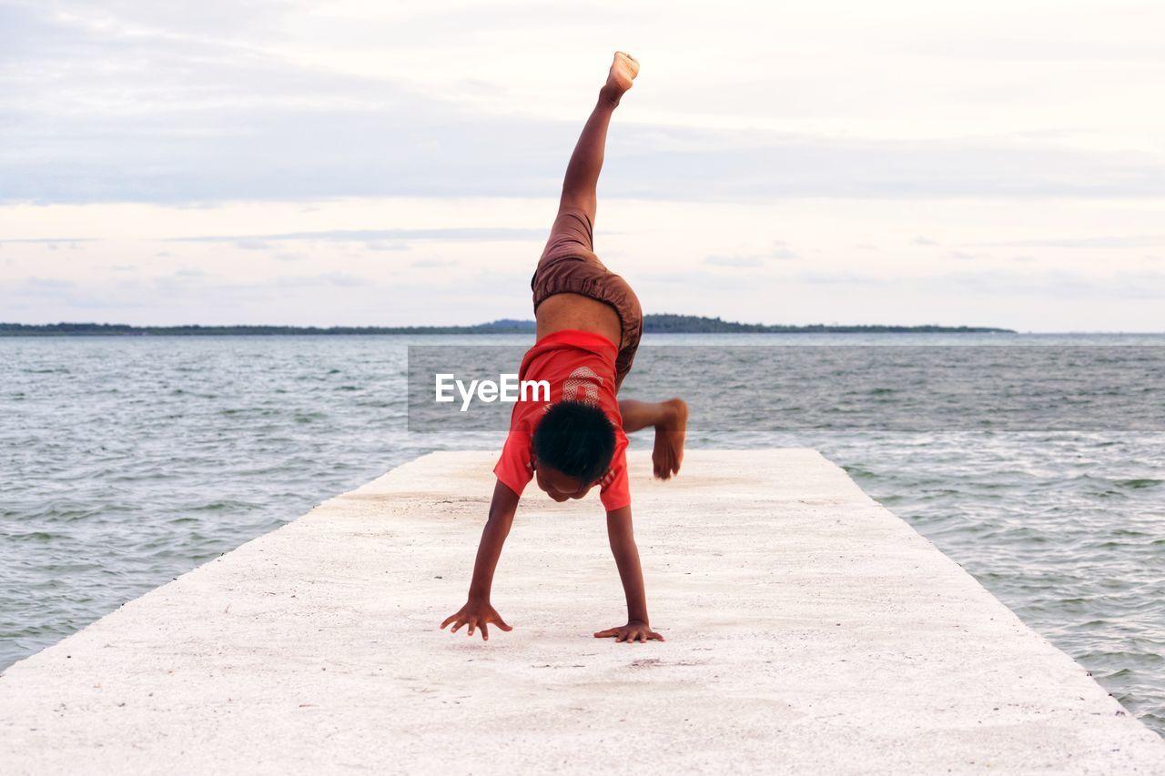 Full Length Of Boy Doing Handstand At Beach Against Sky