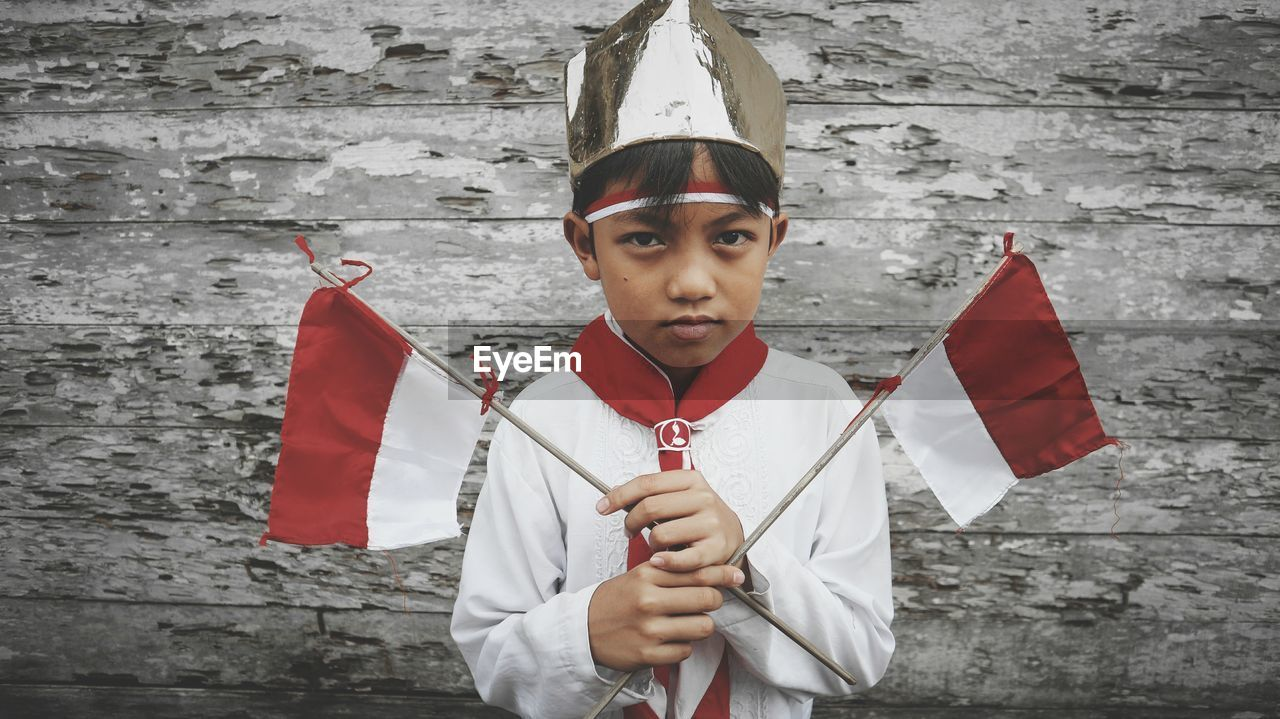 Portrait Of Boy Holding Flag Against Weathered Wall