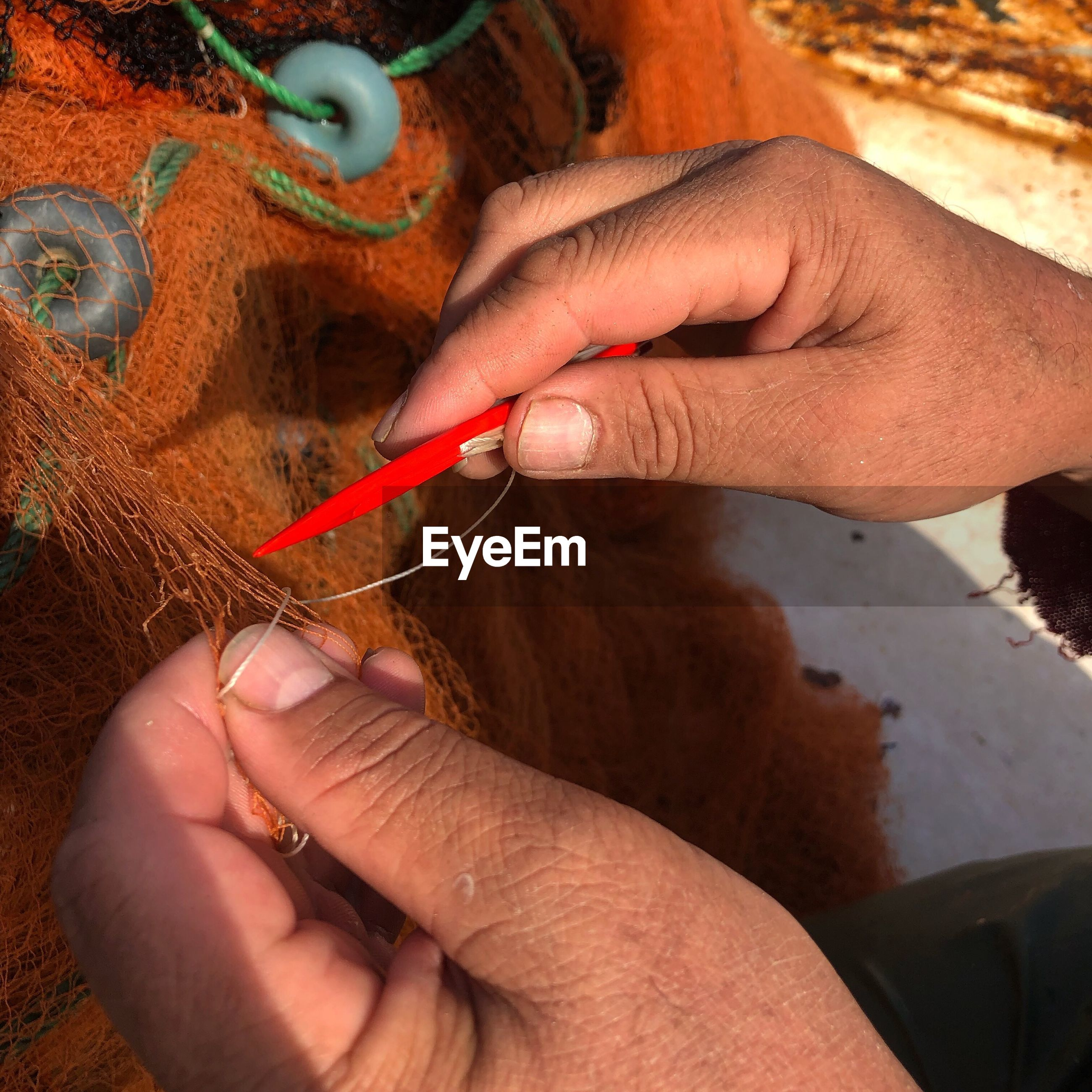 Cropped hands sewing commercial fishing net during sunny day