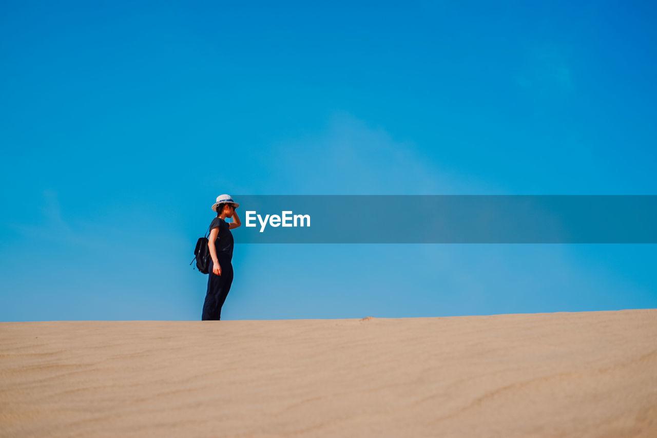 Woman Standing On Desert Against Blue Sky