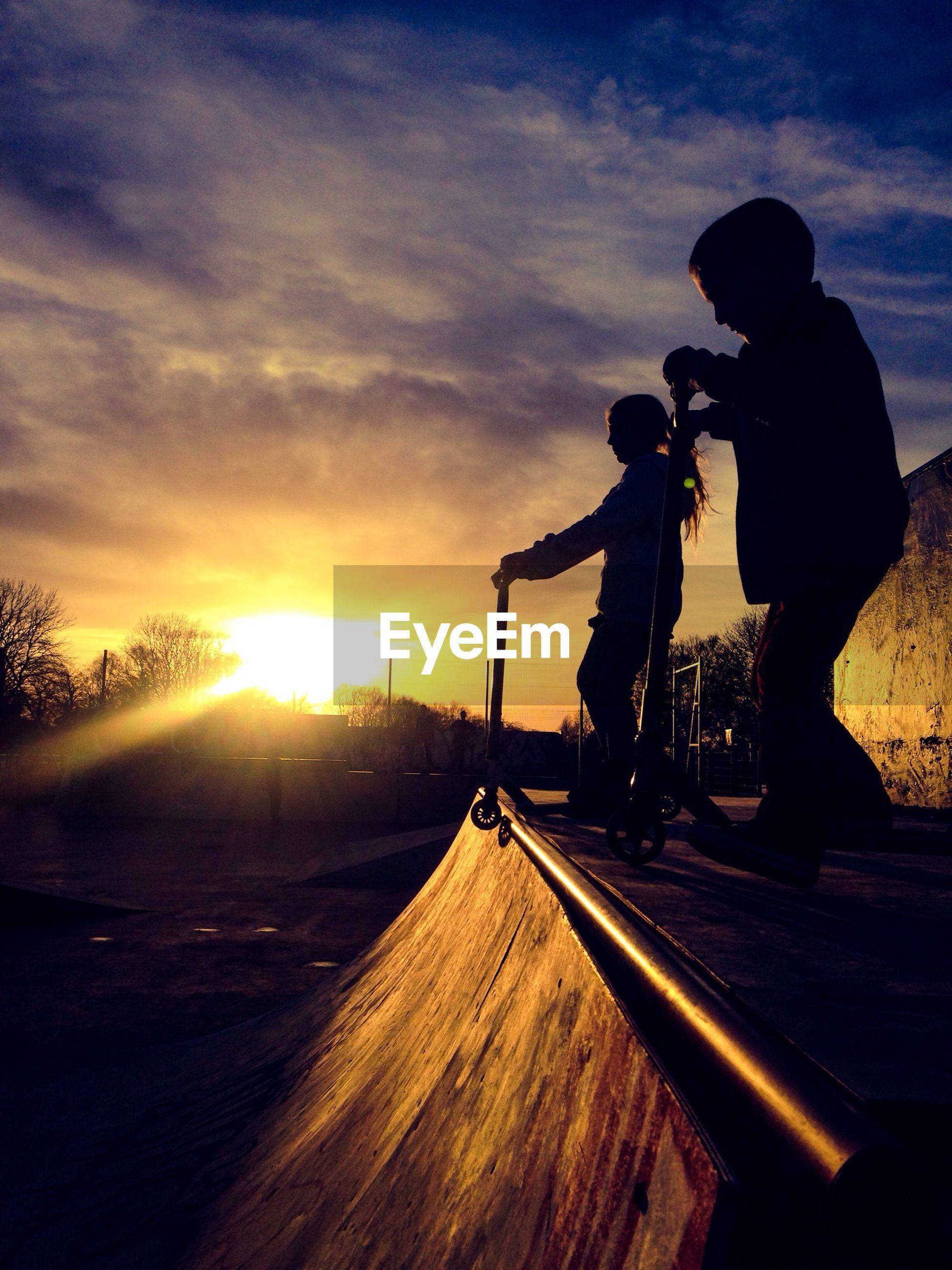 sunset, sun, silhouette, sky, sunbeam, sunlight, lens flare, transportation, cloud - sky, orange color, land vehicle, nature, car, leisure activity, road, tranquil scene, cloud, lifestyles
