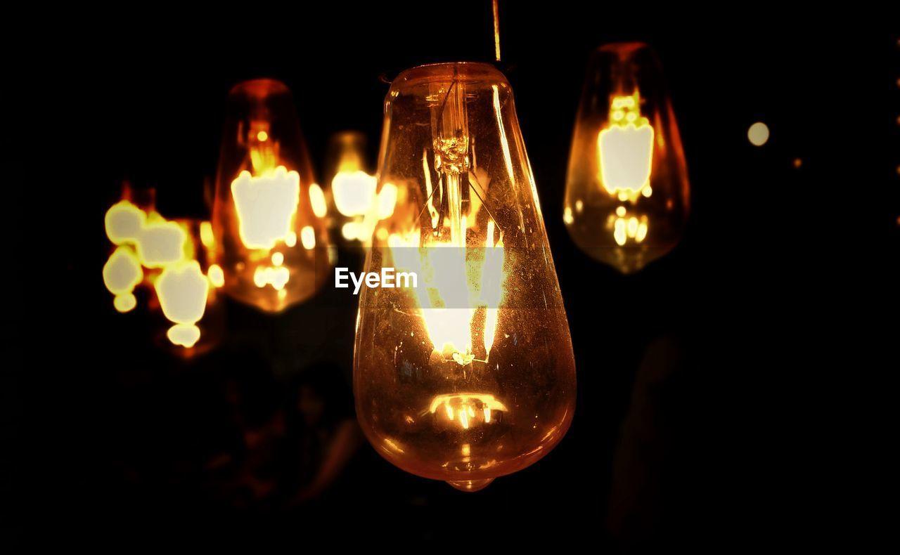 Close-up of illuminated light bulbs in darkroom