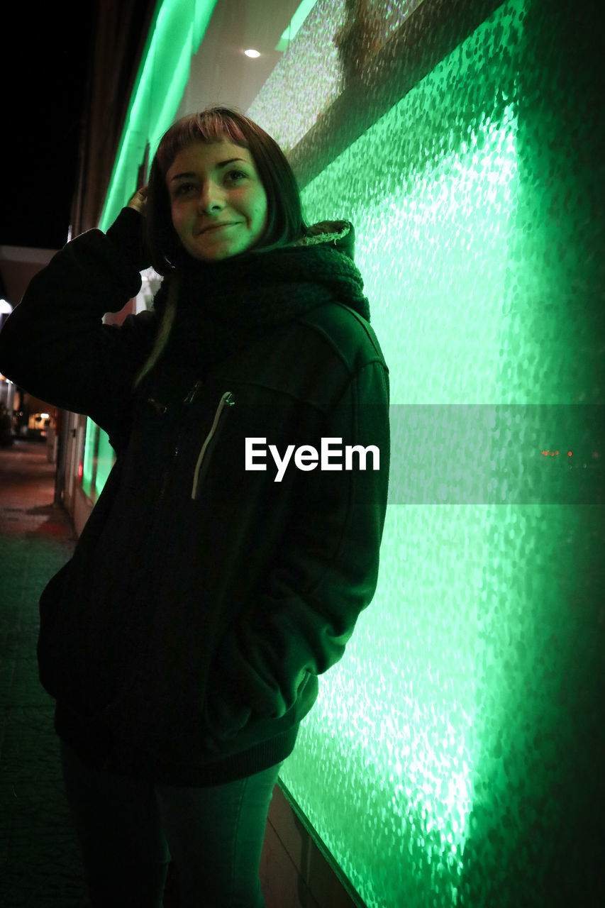 Teenage girl looking away while standing against illuminated wall at night
