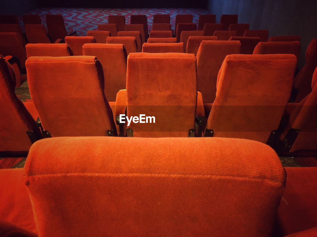 seat, in a row, chair, empty, movie theater, arts culture and entertainment, absence, indoors, repetition, no people, side by side, auditorium, arrangement, theater, order, film industry, red, large group of objects, stage theater
