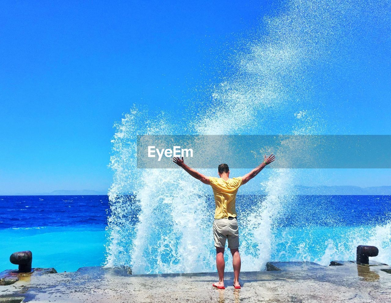 Rear view of man standing with waves splashing on shore in background against clear blue sky