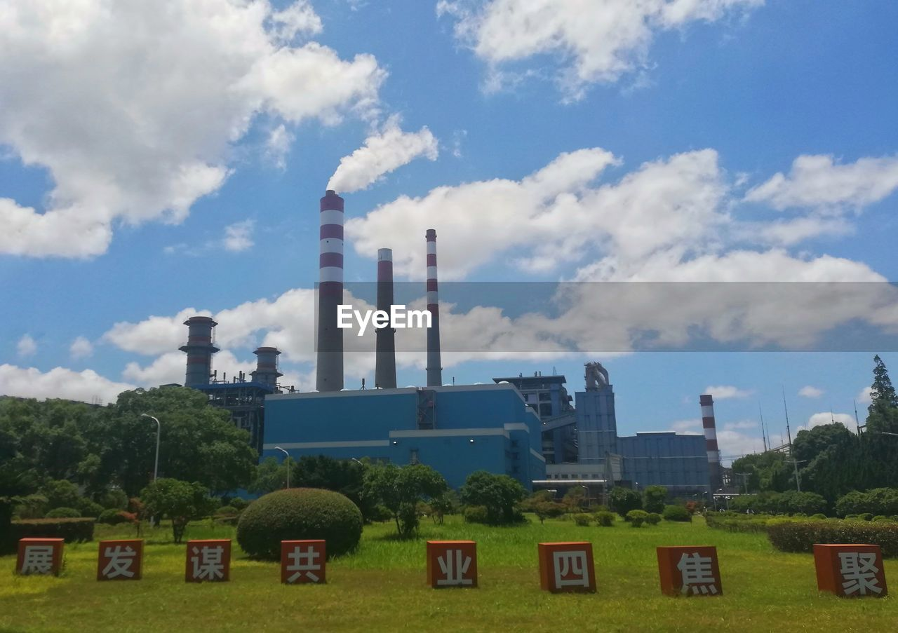 building exterior, built structure, architecture, cloud - sky, sky, factory, industry, smoke stack, day, no people, plant, nature, pollution, tree, outdoors, fuel and power generation, smoke - physical structure, building, chimney, environmental issues, air pollution