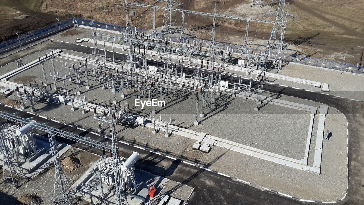 high angle view, industry, architecture, built structure, transportation, factory, fuel and power generation, road, aerial view, day, outdoors, no people, technology, equipment, city, nature, building exterior, connection, mode of transportation, sunlight, industrial equipment