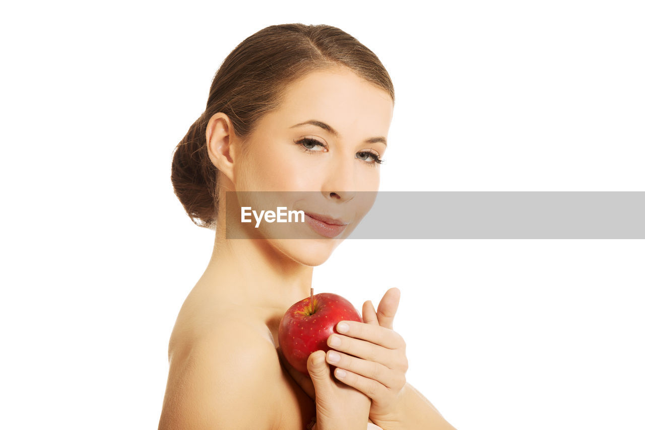 Close-Up Portrait Of Young Woman Holding Apple Against White Background