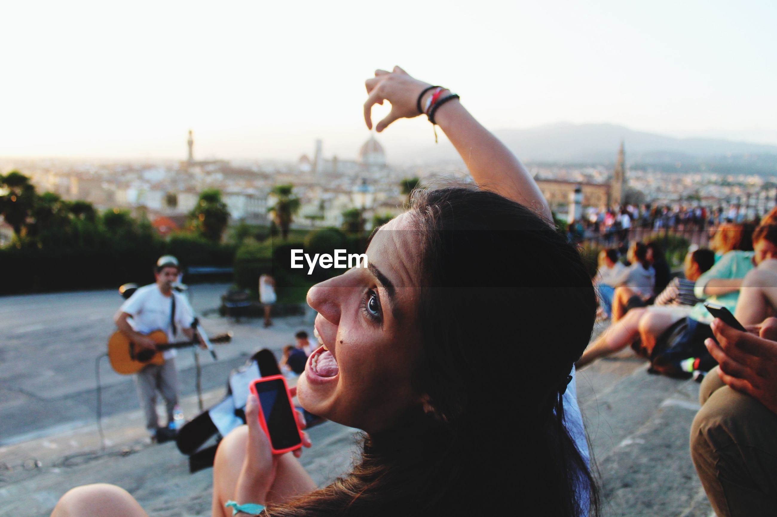 lifestyles, leisure activity, focus on foreground, large group of people, person, clear sky, city, enjoyment, holding, arts culture and entertainment, young adult, crowd, fun, men, cityscape, beach, outdoors, togetherness