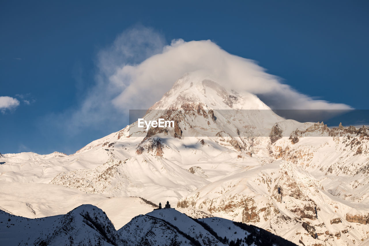 mountain, snow, sky, winter, scenics - nature, snowcapped mountain, beauty in nature, cold temperature, cloud - sky, tranquil scene, mountain range, tranquility, non-urban scene, nature, environment, white color, idyllic, landscape, day, no people, mountain peak, extreme weather, formation