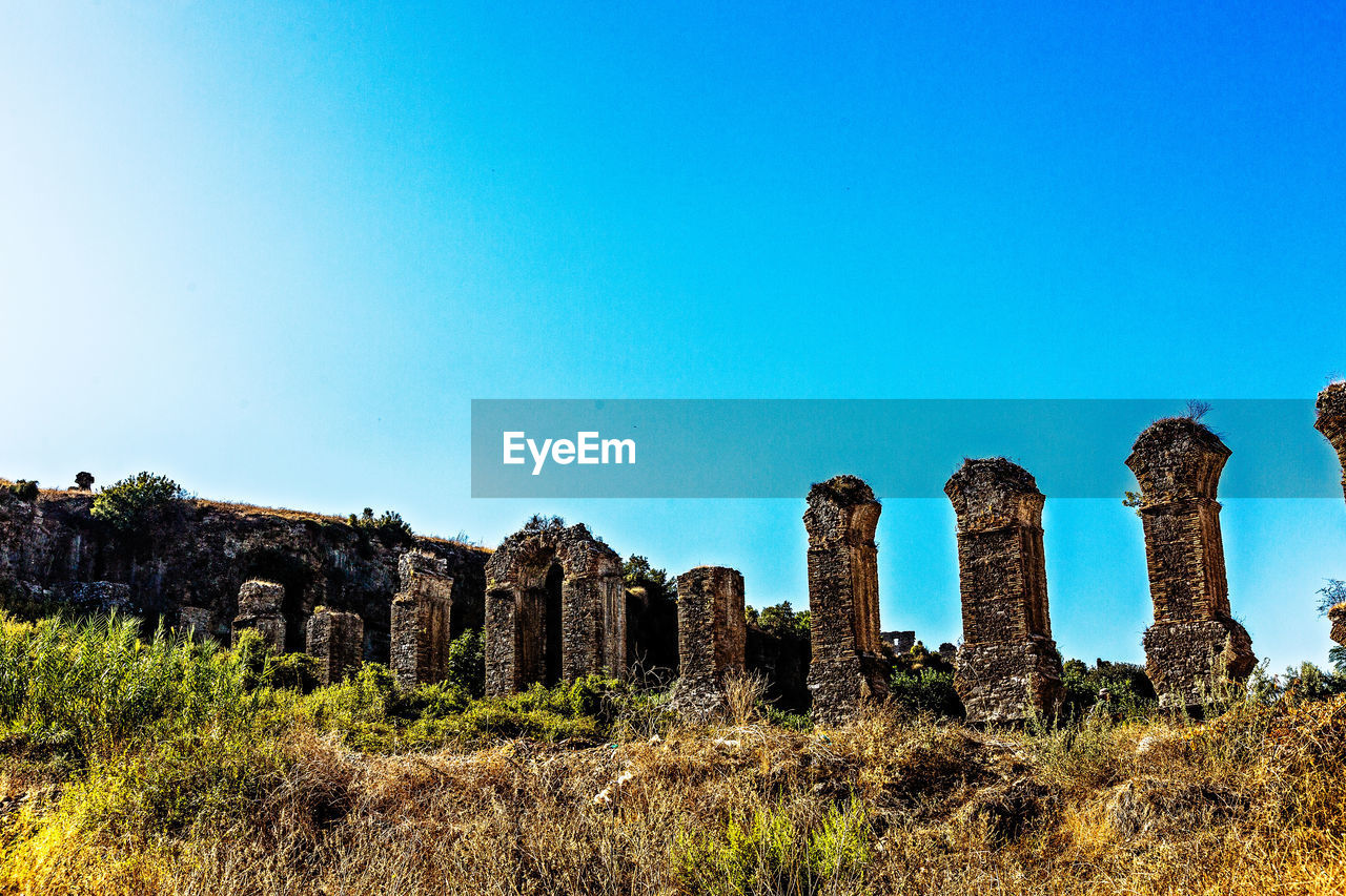 old ruin, ancient, history, architecture, abandoned, the past, archaeology, ancient civilization, damaged, old, copy space, weathered, built structure, bad condition, clear sky, run-down, arch, day, architectural column, travel destinations, outdoors, no people, grass, landscape, building exterior, nature, sky