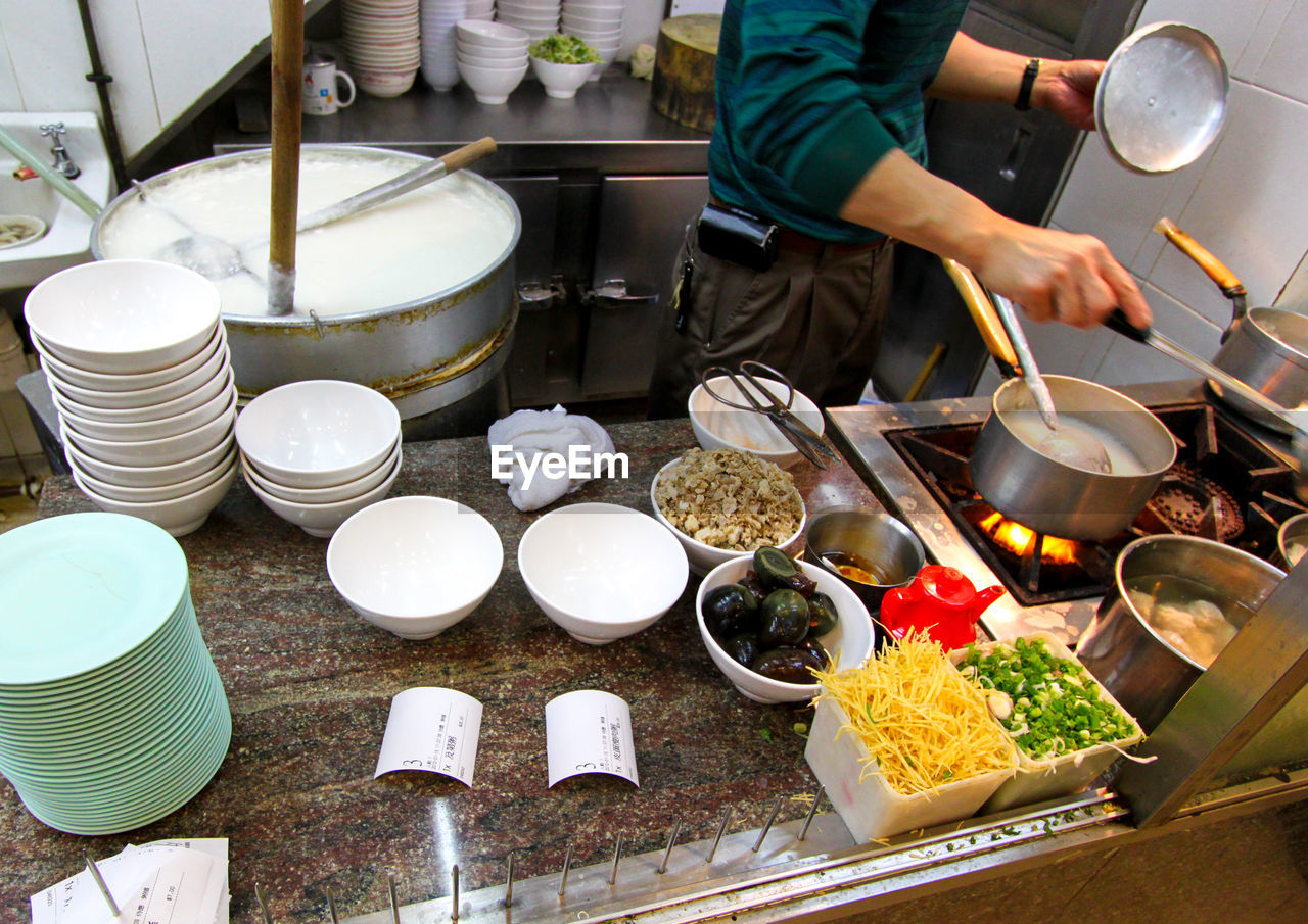 Midsection Of Man Preparing Food In Kitchen At Restaurant