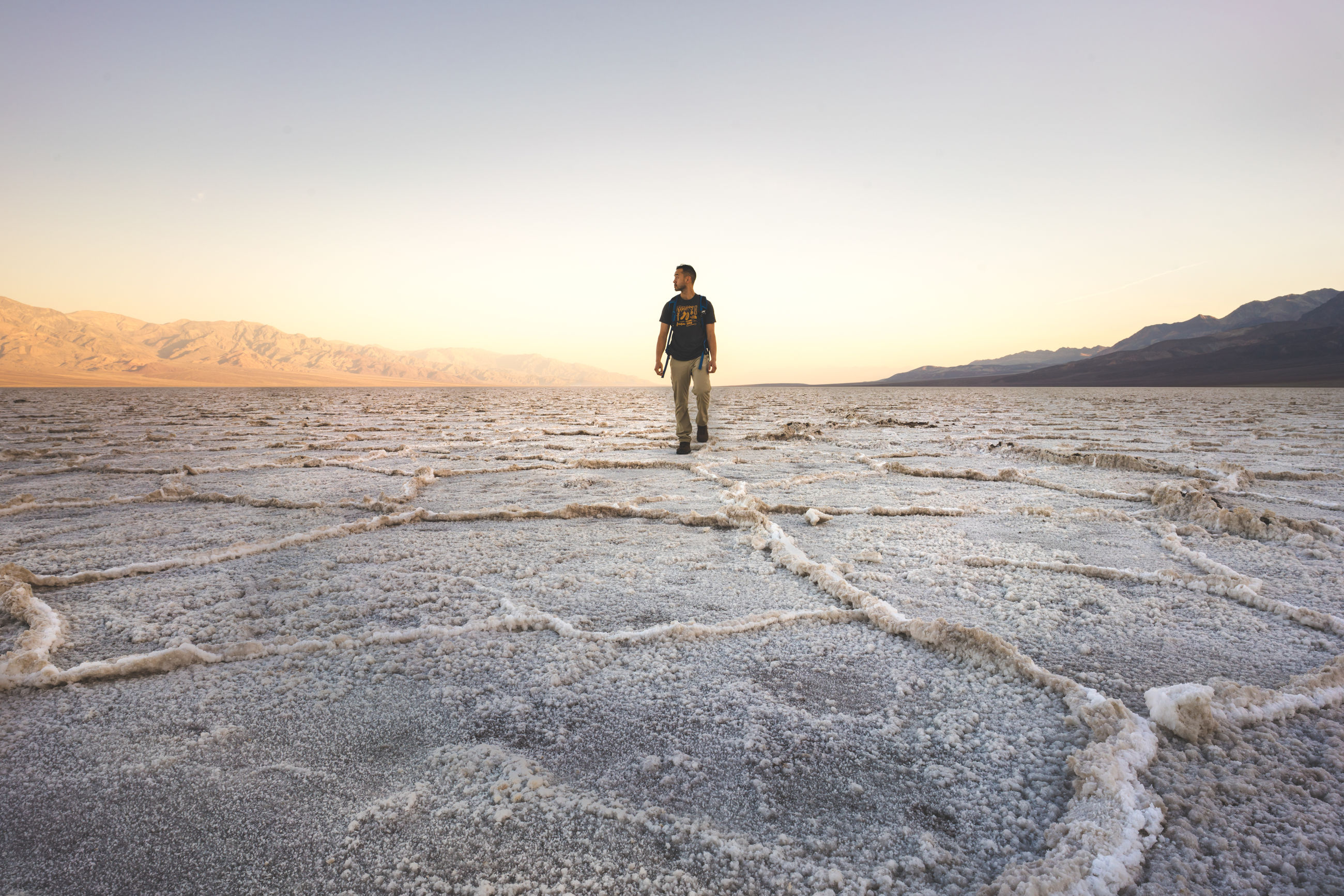 Full length of man walking on salt flat against sky during sunset