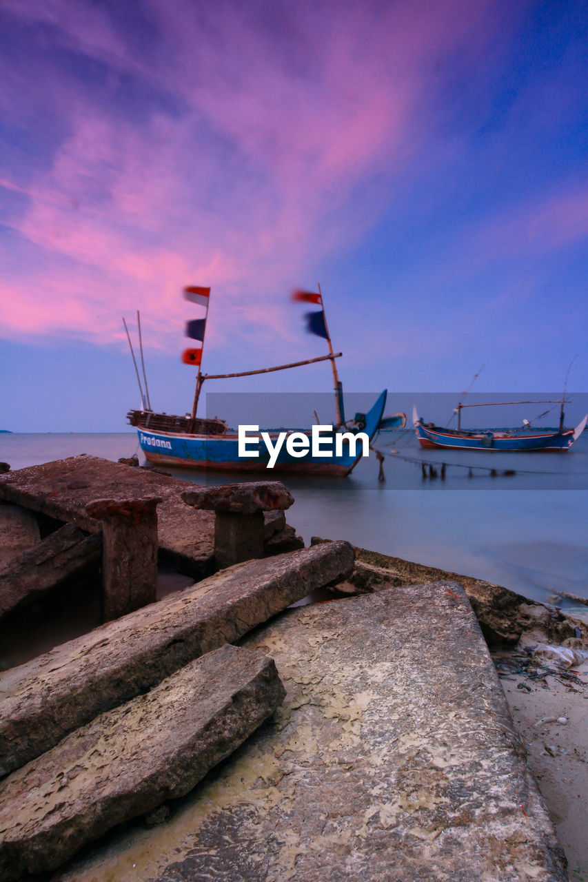nautical vessel, transportation, water, mode of transportation, sky, sea, moored, cloud - sky, nature, no people, scenics - nature, beauty in nature, tranquility, beach, sunset, outdoors, rock, tranquil scene, land, sailboat, fishing boat