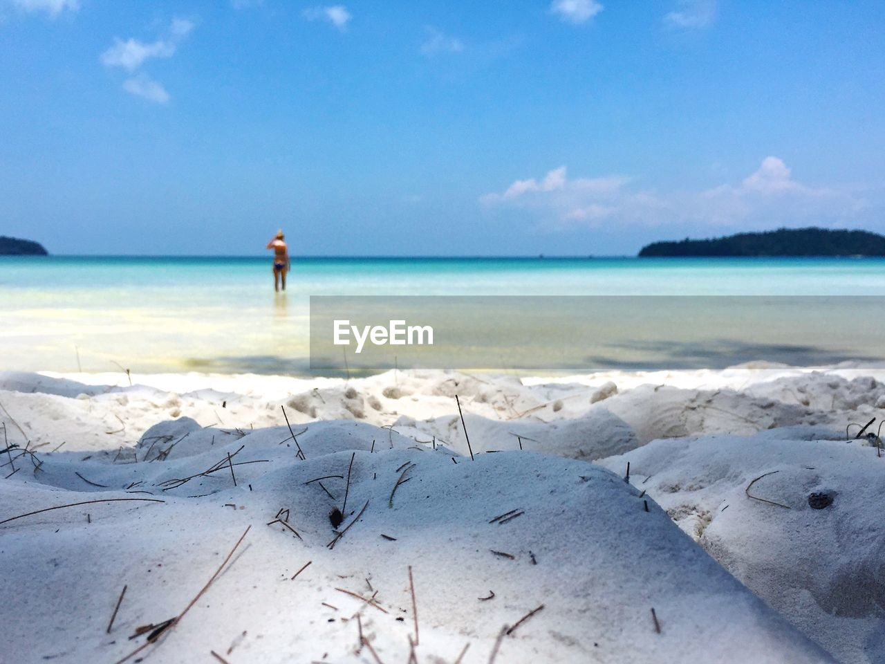 Surface level view of sand with woman standing in sea against sky