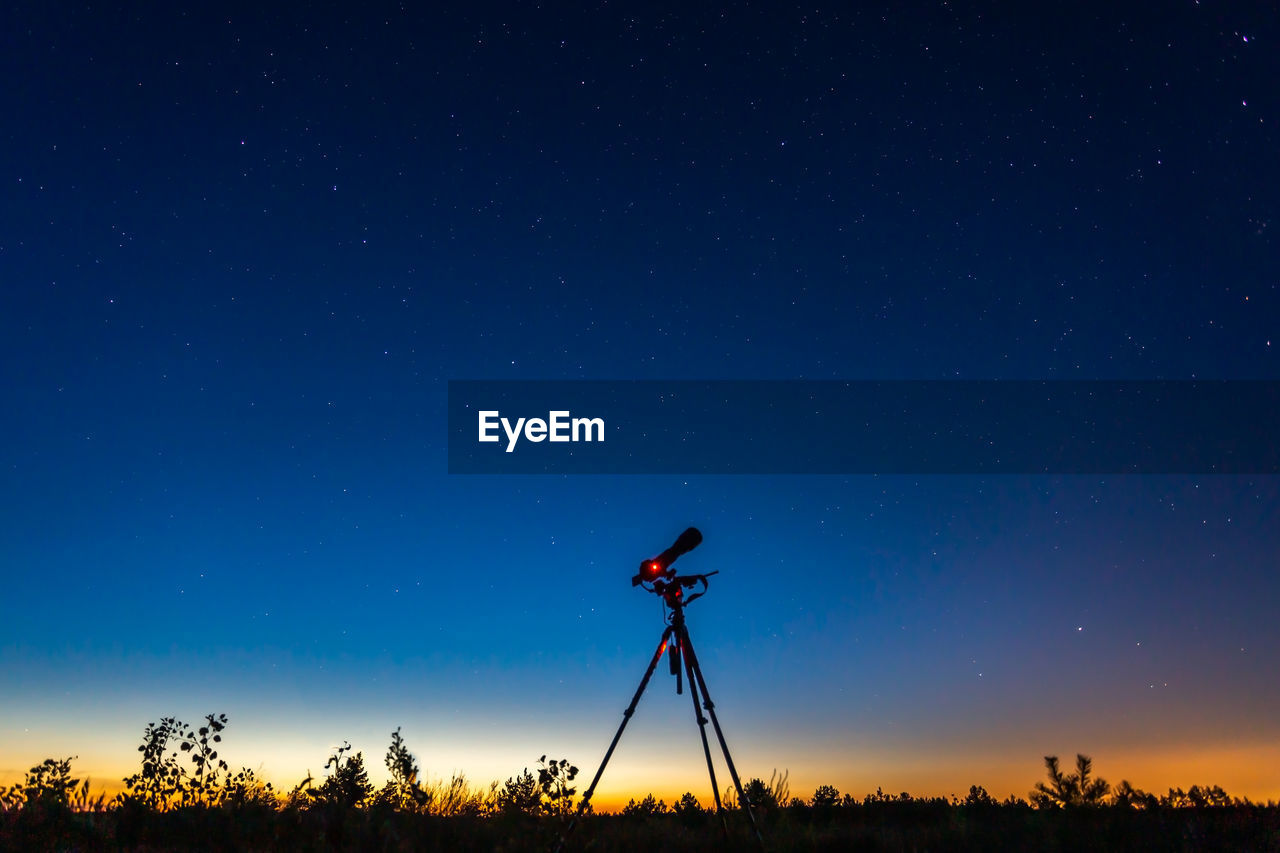 sky, blue, star - space, scenics - nature, silhouette, tripod, technology, night, beauty in nature, nature, field, photography themes, land, astronomy, non-urban scene, tree, landscape, plant, camera - photographic equipment, outdoors, digital camera, photographer