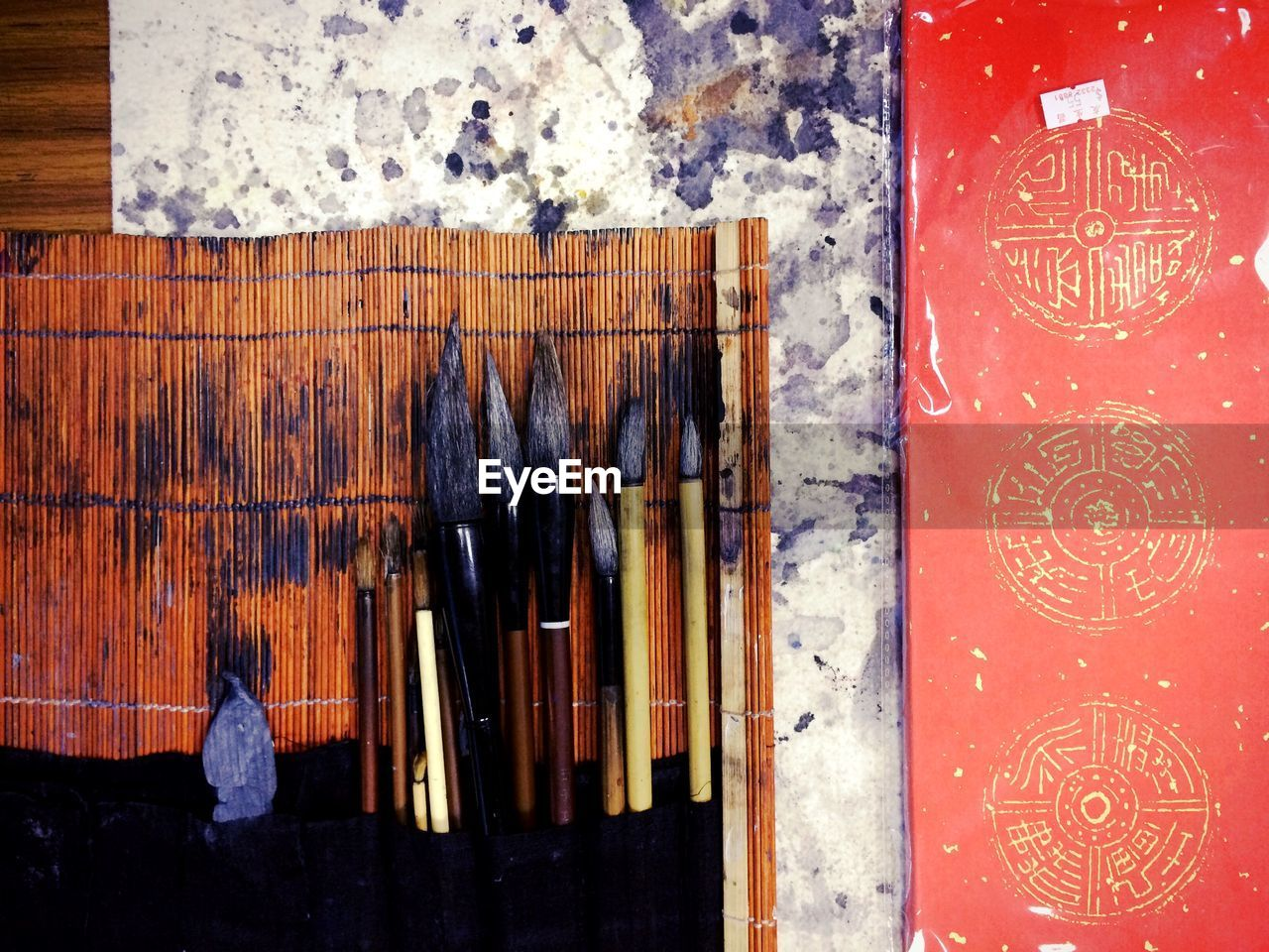Directly Above Shot Of Paintbrushes With Red Book On Table