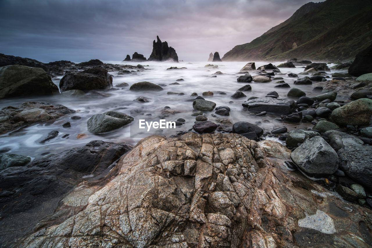 Rocks On Beach During Sunset