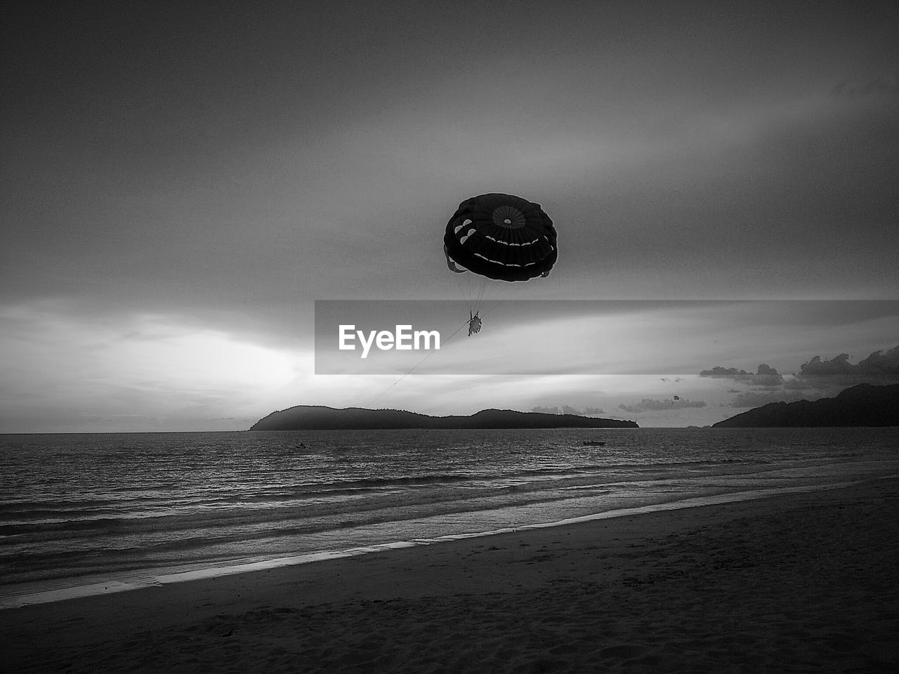 Person paragliding over beach against sky