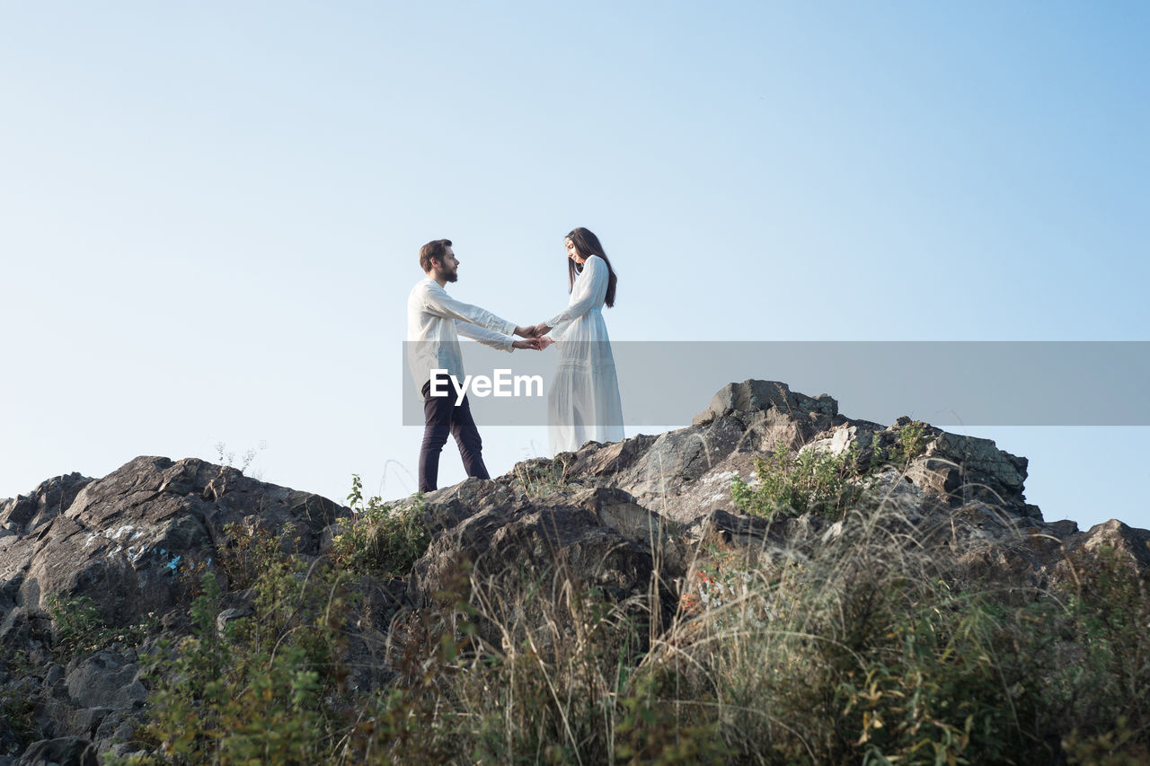 two people, sky, standing, rock, young men, rock - object, real people, young adult, men, couple - relationship, copy space, nature, solid, leisure activity, togetherness, lifestyles, casual clothing, clear sky, people, bonding, outdoors, positive emotion