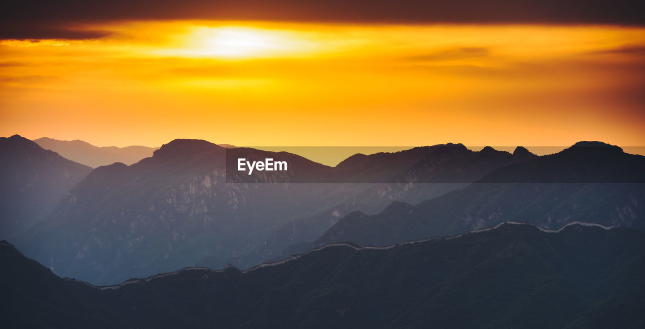 mountain, sunset, beauty in nature, nature, mountain range, orange color, tranquil scene, scenics, no people, tranquility, sky, outdoors, silhouette, cold temperature, winter, landscape, day