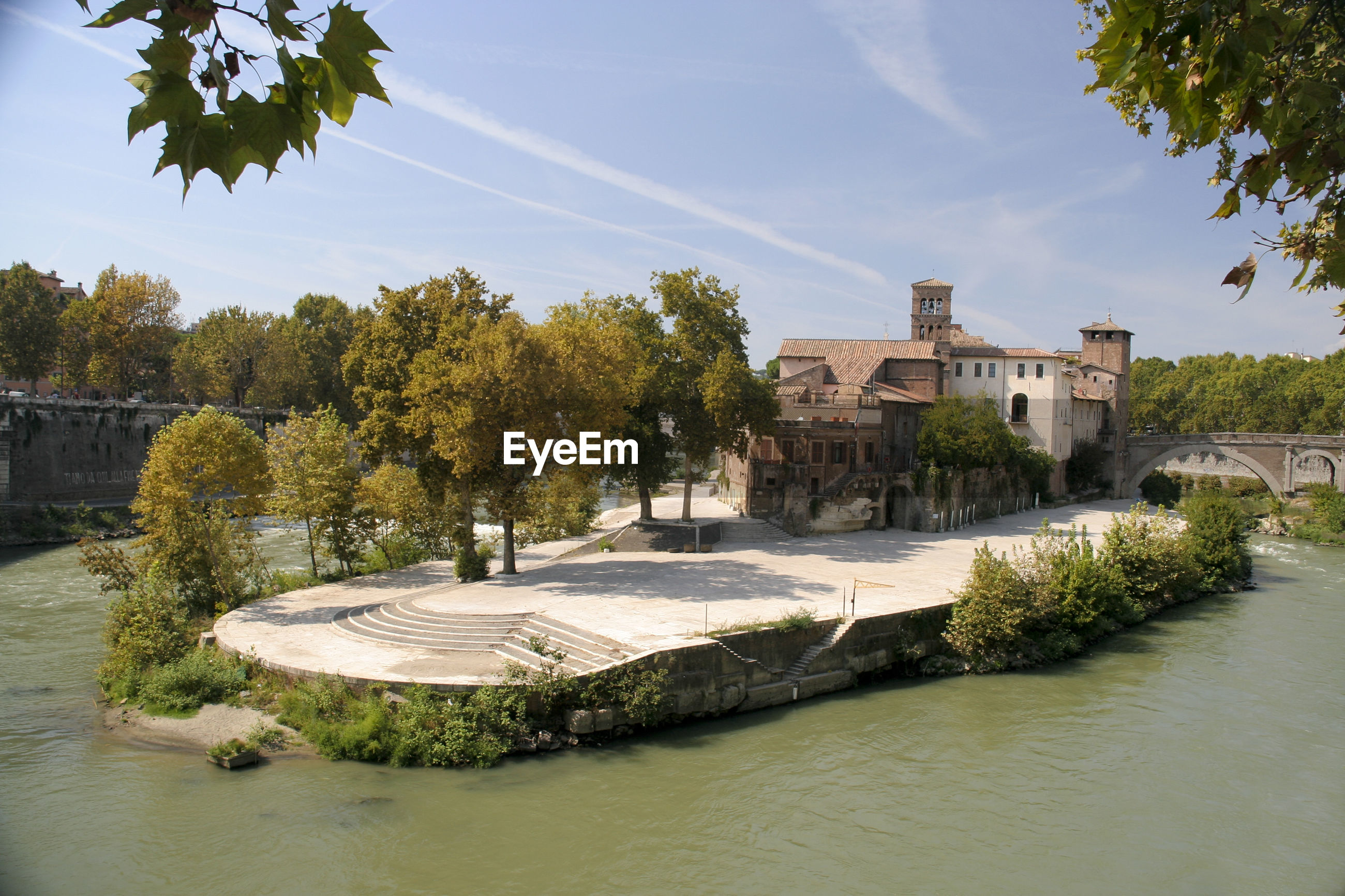 Historic buildings by tiber river against sky
