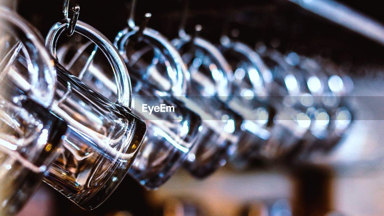 Close-up of glass mugs hanging on rack