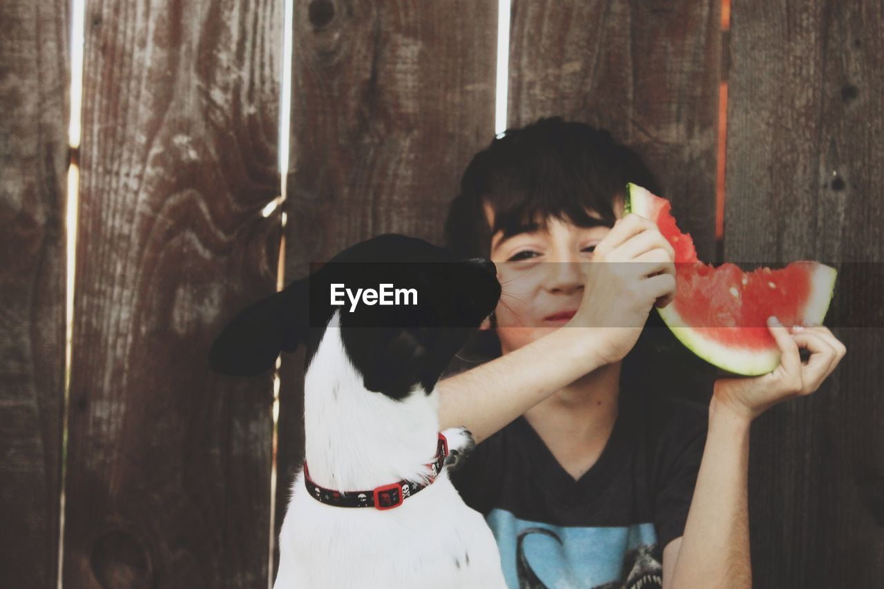 Smiling Holding Watermelon While Sitting With Dog Against Wooden Fence