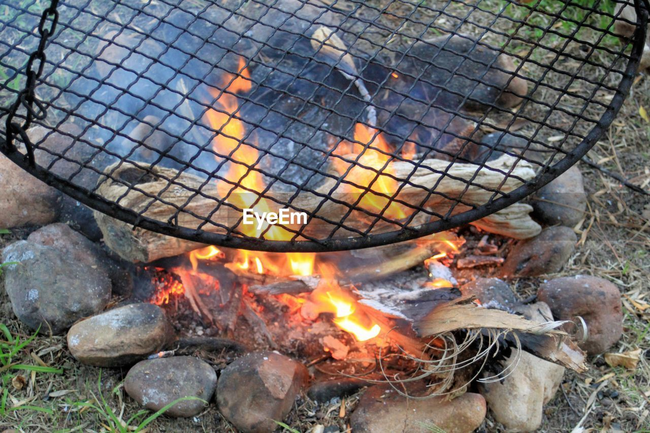 heat - temperature, burning, fire, fire - natural phenomenon, flame, nature, food, day, no people, glowing, food and drink, preparation, barbecue, outdoors, wood - material, log, high angle view, kitchen utensil, camping, bonfire, wood, campfire