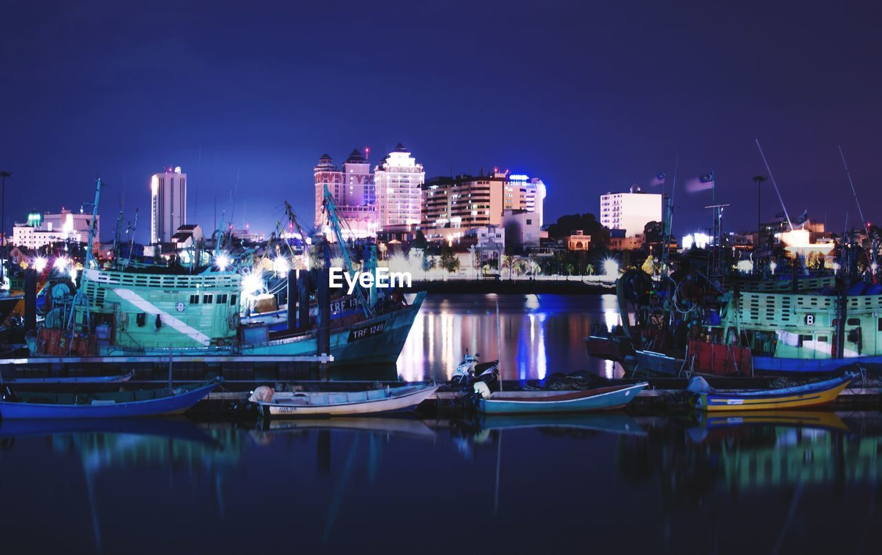 night, illuminated, building exterior, waterfront, architecture, built structure, water, nautical vessel, river, moored, reflection, no people, city, sky, outdoors, cityscape, harbor, clear sky, modern, skyscraper, yacht
