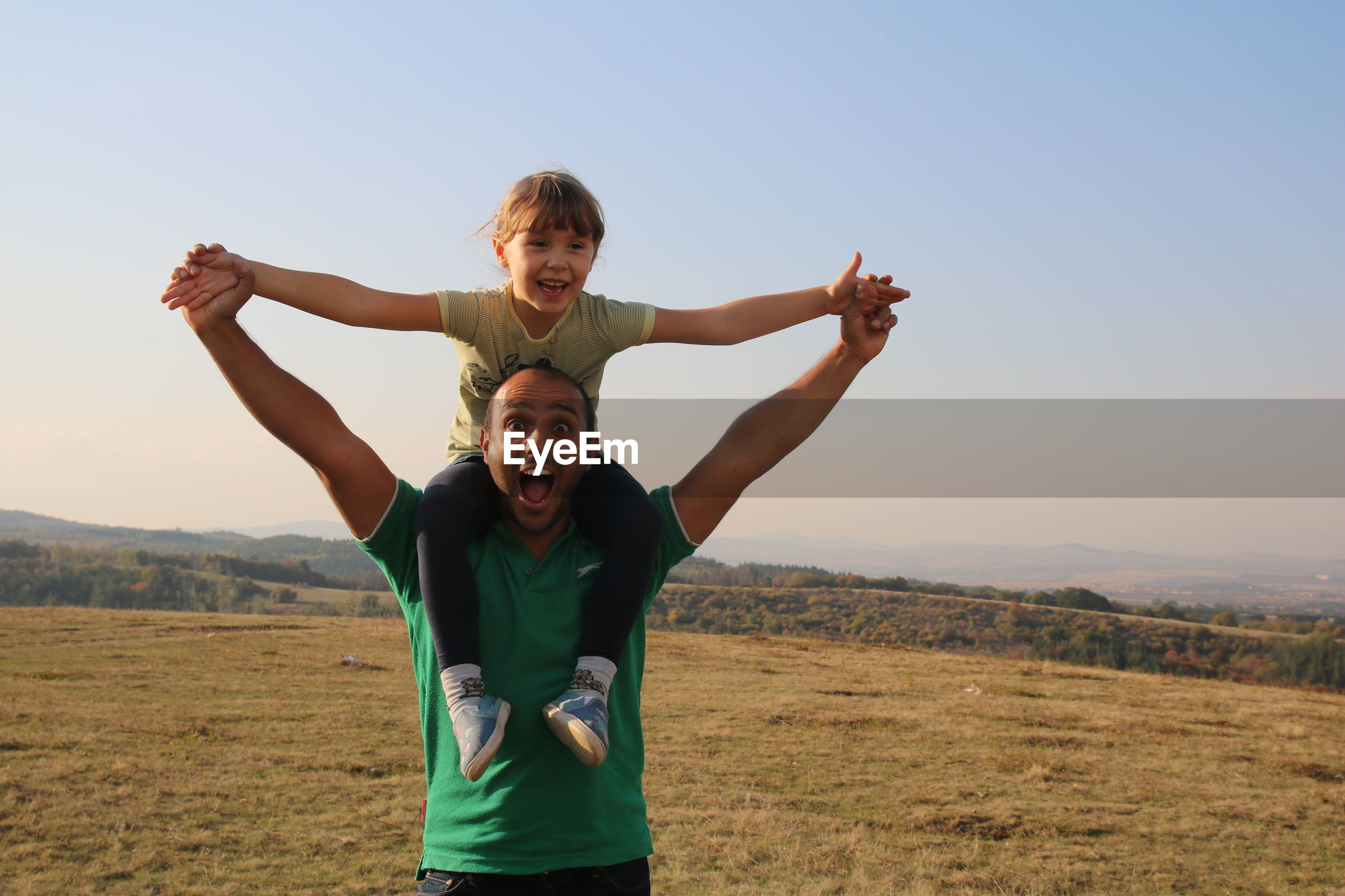 Happy father and daughter playing on field against sky