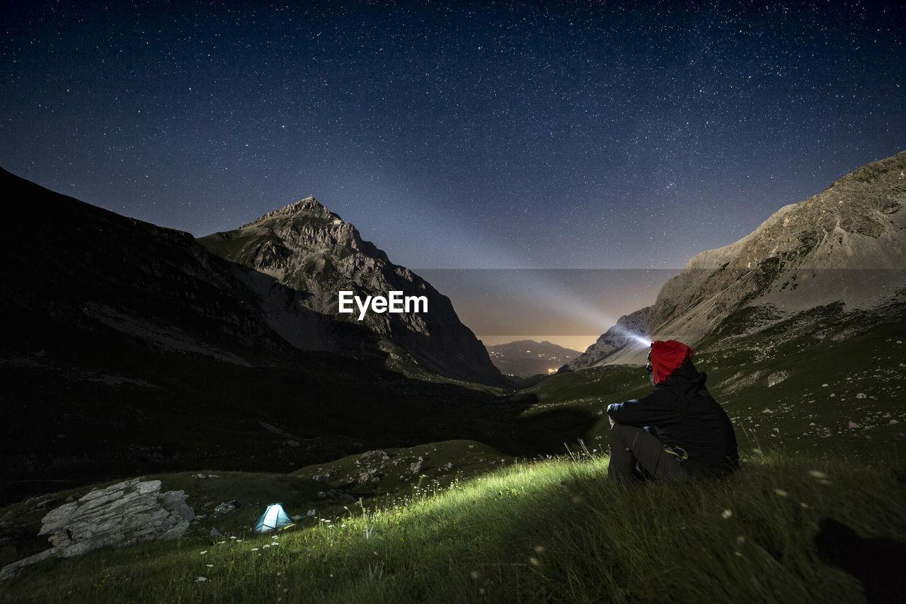 Man With Flashlight Sitting On Mountain At Night